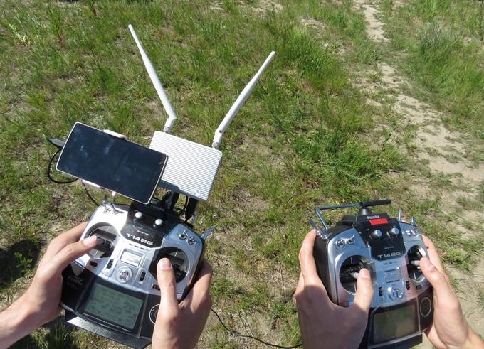 Смартфон крепится к пульту управления скобой и подключается по технологии Wi-Fi, служит сенсорным дисплеем для ДУ. На снимке: пилотирование аппарата DJI S1000+, первый пульт ДУ служит для управления самим октакоптером, второй — для управления камерой во время съёмки