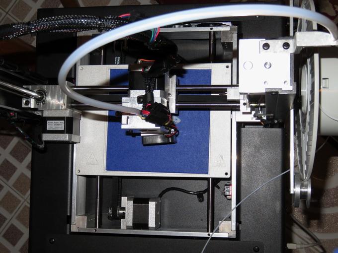 Принтер Inno3D Printer D1 отличается открытой конструкцией (вид сверху). Слева расположена катушка с PLA-нитью, которая по рукаву подается на экструдер