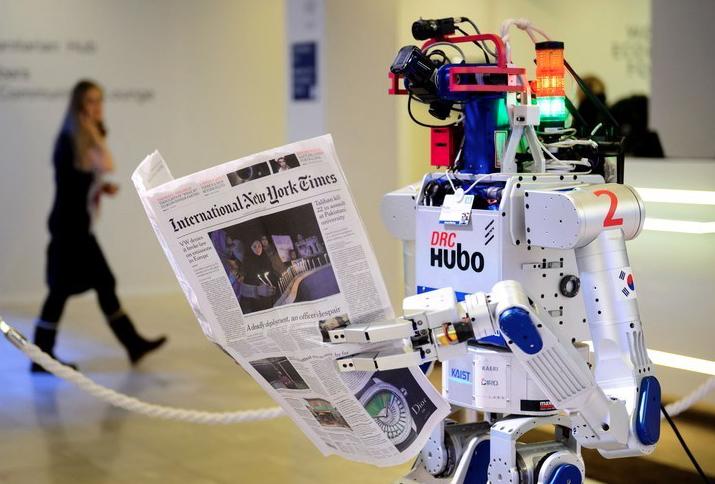 Робот с газетой в руках в ходе выставки на Ежегодном международном экономическом Форуме в Давосе. Фотограф:Fabrice Coffrini / AFP / Getty Images