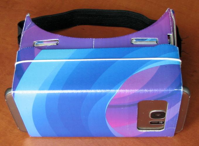 Очки Cardboard вместе со смартфоном в сборе. Для камеры предусмотрена прорезь в картонной крышке