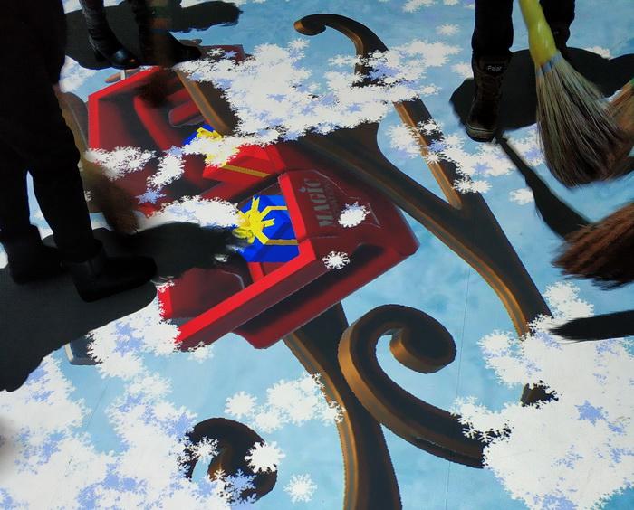 Відвідувачі змітають звичайними віниками віртуальний сніг з підлоги