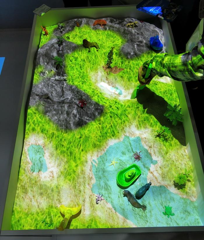 Інтерактивна пісочниця Briolight S. Насправді увесь кольоровий рельєф, який ви тут бачите, сформований зі звичайного сірого піску. Якщо лопаткою пересипати пісок з місця на місце — проектор буде автоматично змінювати його забарвлення в залежності від висоти рельєфа